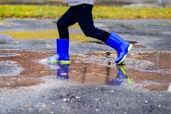 Boy in rubber blue rainboots jumping to dirty puddle. Happy little boy in rubber blue rainboots jumping to dirty puddle. Rainy autumn day Royalty Free Stock Images