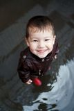 Boy in rubber boots plays at a puddle royalty free stock photography