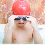 Boy in rubber cap taking off goggles Royalty Free Stock Image