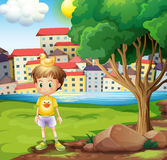 A boy with a rubber duck above his head standing near the tree Stock Photos
