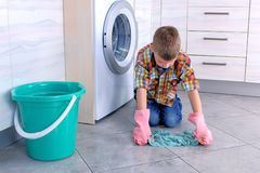 Boy in rubber gloves washes the floor in the kitchen. Child`s home duties. Boy in rubber gloves washes the floor in the kitchen. Child`s home duties royalty free stock photography