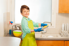 Boy in rubber gloves washing plates with sponge Royalty Free Stock Photography