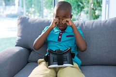 Boy rubbing eyes while sitting with VR headset on sofa Royalty Free Stock Images