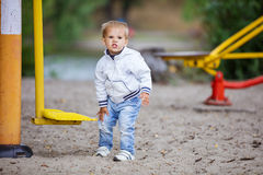 Boy rubbing his leg hit by outdoor exercise machine Royalty Free Stock Photos