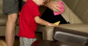 Cute boy playing by sofa with parent stock footage