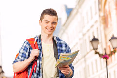 Boy with rucksack and city map on the street Stock Image