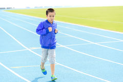 Boy run in blue track Stock Images