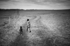 The boy runing with the dog. Black and white picture. The boy runing with the dog Stock Photos