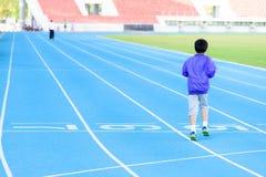Boy runnin on blue track Stock Photography