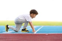 Boy runnin on blue track Royalty Free Stock Photo
