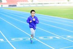 Boy runnin on blue track Stock Images