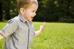 Boy running across field Royalty Free Stock Photography