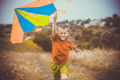 Boy running across the field with kite flying over his head Royalty Free Stock Images