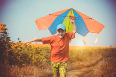 Boy running across the field with kite flying over his head Stock Photography