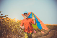 Boy running across the field with kite flying over his head Royalty Free Stock Photo
