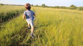 Boy running across hill in slowmotion stock footage