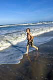 Boy is running along the beach Royalty Free Stock Photography