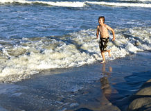 Boy is running along the beach Stock Image