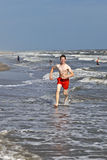 Boy running along the beach in the waves Royalty Free Stock Images