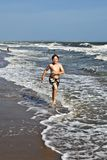 Boy running along the beautiful beach in the waves Royalty Free Stock Photos