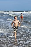 Boy running along the beautiful beach in the waves Stock Photo