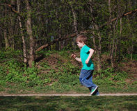 Boy running along the forest path. Active start Royalty Free Stock Photos