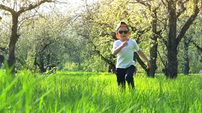 Boy running along the high grass in the garden, tall grass, slow motion stock video