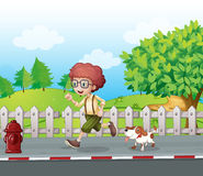 A boy running along the road with his pet Royalty Free Stock Photos