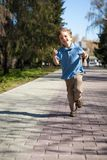 Boy running along road in park Royalty Free Stock Photo
