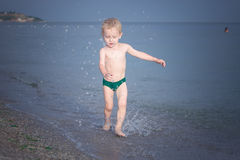 Boy running along the water on the beach Stock Photography