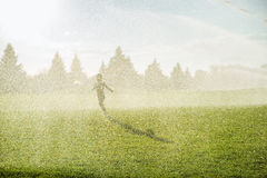 Boy running around the golf courses, which are watered with fountains Stock Photos