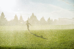 Boy running around the golf courses, which are watered with fountains Royalty Free Stock Image