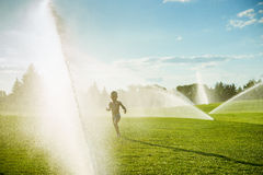 Boy running around the golf courses, which are watered with fountains Stock Image