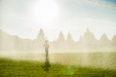 Boy running around the golf courses, which are watered with fountains Royalty Free Stock Photos