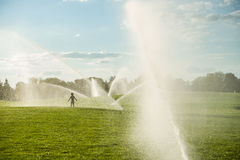 Boy running around the golf courses, which are watered with fountains Stock Photography
