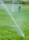 Boy Running around Water Sprinklers Stock Images