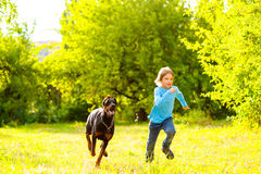 Boy running away from dog or doberman in summer Royalty Free Stock Photo