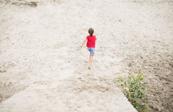 Boy running barefoot at the beach Stock Images
