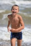 Boy running on the beach Stock Images