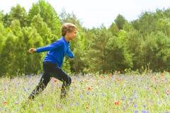 Boy running on beautiful meadow field. Stock Photography
