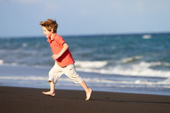 Boy running at black sand beach Royalty Free Stock Image
