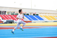 Boy running on blue track Stock Image