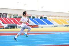 Boy running on blue track Stock Image