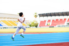 Boy running on blue track Royalty Free Stock Photos