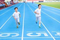 Boy running on blue track Royalty Free Stock Image