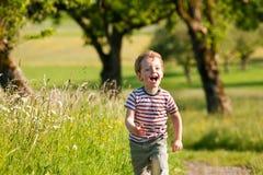 Boy running down a dirtpath stock photos