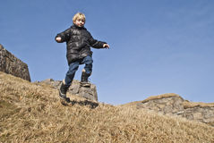 Boy running down a hill at the fortress. My grandson of eight years find it very exciting to be with his grandfather at Fredriksten fortress to explore the Stock Image