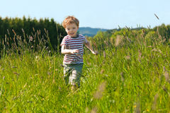 Boy running down a meadow Royalty Free Stock Photo