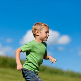 Boy running down a meadow. Little boy running down a meadow in a beautiful landscape in summer royalty free stock image