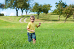 Boy running down a meadow. Little boy running down a meadow in a beautiful landscape in summer stock images